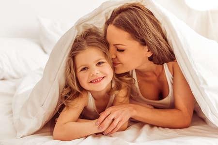 Beautiful young mother is kissing her daughter in cheek, lying in bed under the blanket. Little girl is looking at camera and smiling