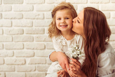 Beautiful young mother is holding flowers and kissing her cute little daughter, against white brick wall. Little girl is smiling