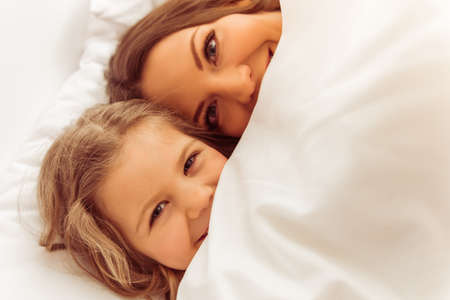 CHILD CARE: Sweet little girl and her beautiful young mother are hiding under the blanket and smiling while lying in bed at home