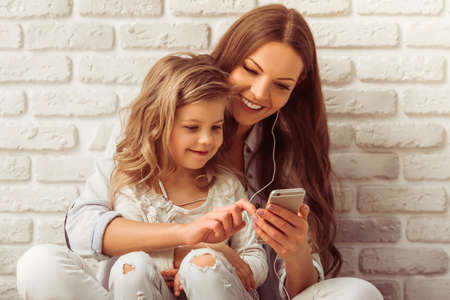 lady on phone: Beautiful young mother and her cute little daughter are listening to music using a smart phone and smiling, against white brick wall