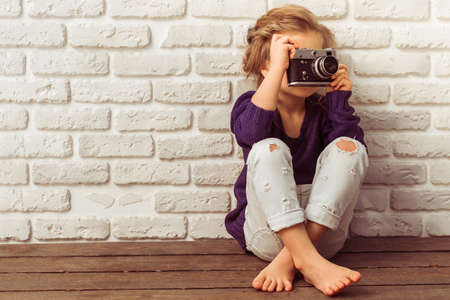 barefoot girls: Beautiful little girl in casual clothes is taking a photo using a camera, sitting against white brick wall