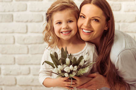 giving gift: Beautiful young mother and her cute daughter are looking at camera and smiling, against white brick wall. Little girl is holding flowers