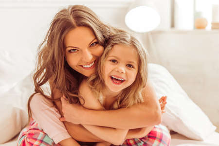sweet dreams: Sweet little girl and her beautiful young mother are hugging, looking at camera and smiling while sitting on bed under the blanket