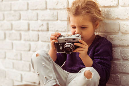 Beautiful little girl in casual clothes is holding a camera, sitting against white brick wall