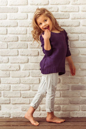 Beautiful little girl in casual clothes is showing surprise, looking at camera and smiling, standing against white brick wall