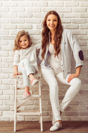 little: Beautiful young mother and her cute little daughter are looking at camera and smiling, sitting against white brick wall Stock Photo