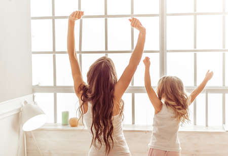 sweet home: Back view of beautiful young mother and her cute little daughter stretching and yawning in the morning