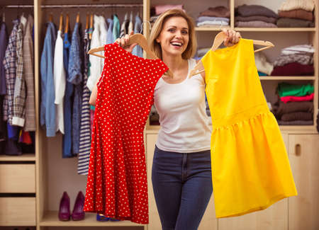 Beautiful girl is smiling and looking at camera while choosing dresses in her dressing room