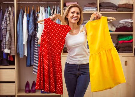 La muchacha hermosa está sonriendo y mirando a la cámara mientras que la elección vestidos en su camerino