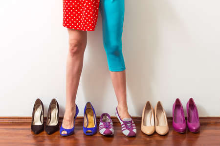 high heeled shoe: Beautiful girl with one leg in sports shoe and another in high heeled shoe is standing in a row with dress shoes, cropped