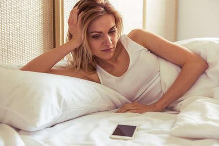 femme triste: Vue de côté de la belle jeune fille regardant un téléphone mobile en position couchée dans son lit Banque d'images