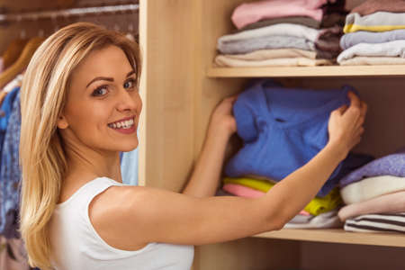 pullover: Beautiful girl is smiling and looking at camera while choosing pullover in her dressing room