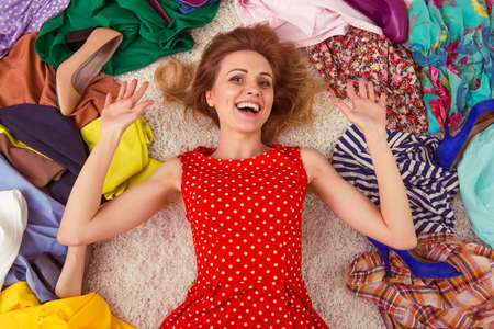 La muchacha hermosa está sonriendo, tendido entre los zapatos de tacón alto y ropa de moda en el suelo en un vestidor