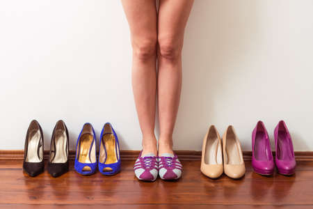 high heeled shoes: Beautiful girl in sports shoes is standing in a row with high heeled shoes, cropped