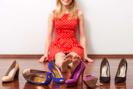 high  heeled: Beautiful girl in red dress is sitting among high heeled shoes in a dressing room, cropped Stock Photo