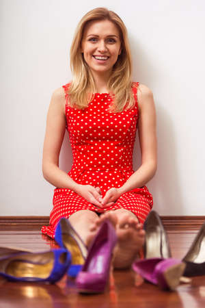 high heeled shoes: Beautiful girl in red dress is looking at camera and smiling while sitting among high heeled shoes in a dressing room