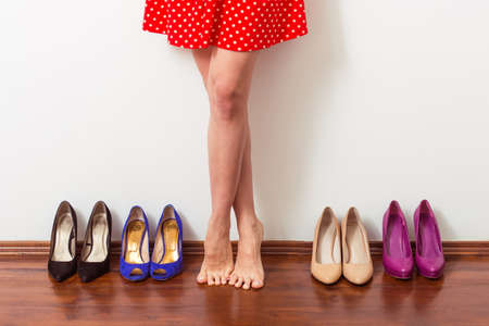 high  heeled: Beautiful barefooted girl is standing in a row with high heeled shoes, cropped