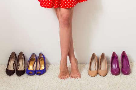 pies descalzos: Hermosa chica descalza est� de pie en una fila con zapatos de tac�n alto, recortada Foto de archivo