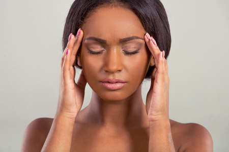 girl with gray eyes: Portrait of beautiful tired Afro American girl with closed eyes massaging her temples, on a gray background