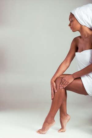 american sexy: Вид сбоку красивая афро американская девушка в полотенце касаясь ее ноги, сидя на сером фоне