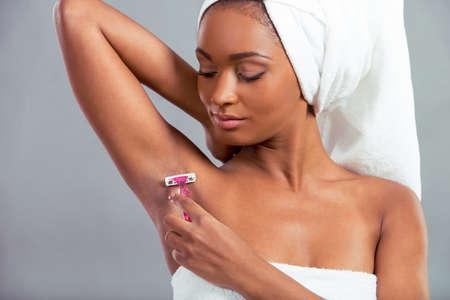 cabeza femenina: Hermosa niña afroamericana con una toalla sobre su cabeza está afeitando su axila, sobre un fondo gris Foto de archivo