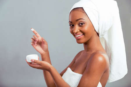 healthy looking: Side view of beautiful Afro American girl with a towel on her head holding a jar of cream, looking at camera and smiling, on a gray background