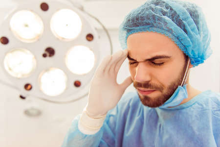 keeping room: Handsome young doctor is keeping hands on forehead, having a headache, in a modern operating room, close up