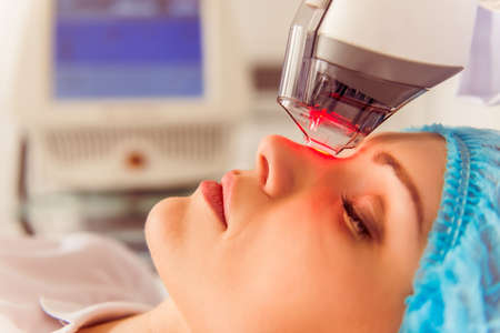 Beautiful female patient is getting a face skin treatment while lying at cosmeticians office, close up Stock Photo