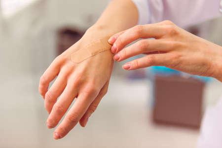 herida: Mano con yeso adhesivo que cubre una herida leve, primer plano
