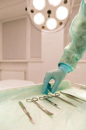 minimally: A surgeon is choosing a medical instrument, close up. Modern operating room in the background