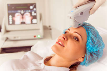 Beautiful female patient is getting a treatment while lying at cosmeticians office Reklamní fotografie