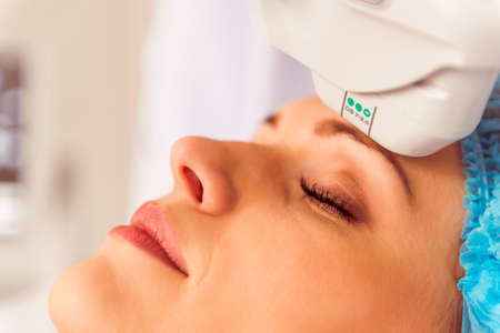 Beautiful female patient is getting a treatment while lying at cosmeticians office, close up Reklamní fotografie