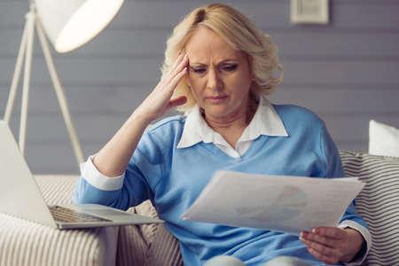 De mooie vermoeide oude vrouw in vrijetijdskleding houdt documenten terwijl thuis het werken met laptop