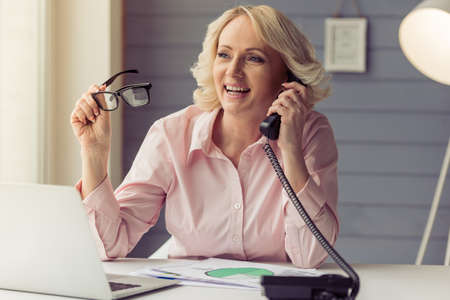 Beautiful old woman in classic shirt is talking on the phone, holding eyeglasses and smiling while working with a laptop at home Stock Photo