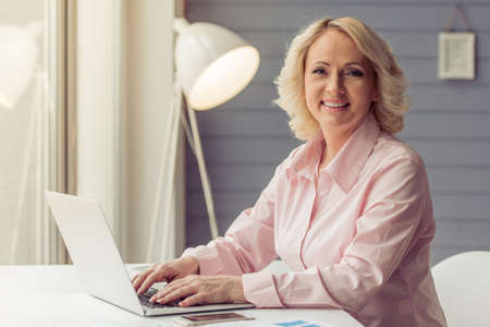 Beautiful old woman in classic shirt is using a laptop, looking at camera and smiling while working at home