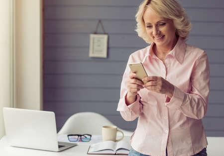 De mooie oude vrouw in klassiek overhemd gebruikt een mobiele telefoon en glimlacht terwijl status dichtbij haar werkende plaats Stockfoto
