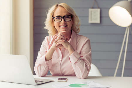 Beautiful old woman in classic shirt and glasses is looking at camera and smiling while working with a laptop at home