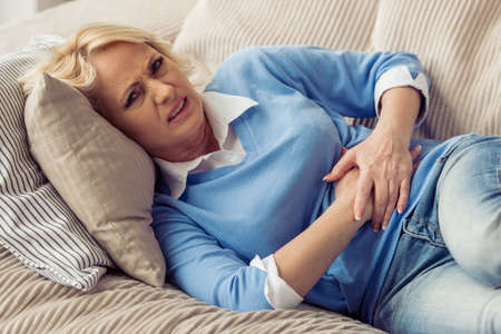 Beautiful tired old woman in casual clothes is having a stomach ache while lying on couch at home