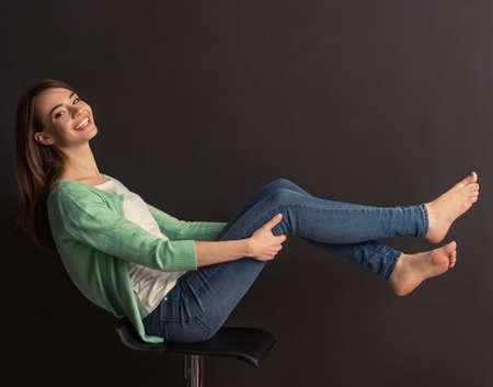 Vista laterale di giovane e bella ragazza in cerca di fotocamera e sorridente, seduta con le gambe sollevate sulla sedia contro sfondo scuro