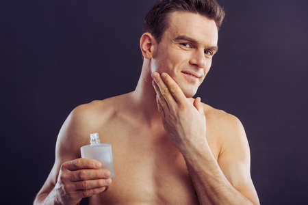 aftershave: Portrait of handsome man smiling, holding aftershave lotion and applying it, on a dark background