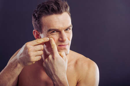 Portrait of handsome man squeezing pimples, on a dark background Stock Photo