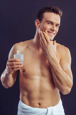 aftershave: Handsome man is smiling, holding aftershave lotion and applying it, on a dark background Stock Photo
