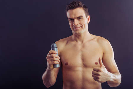 adult armpit: Portrait of handsome man holding a spray antiperspirant and showing Ok sign, on a dark background Stock Photo