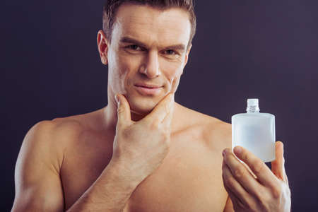aftershave: Portrait of handsome man holding aftershave lotion, looking at camera and smiling, on a dark background