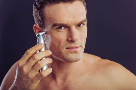 touching noses: Portrait of handsome man using a hair trimmer for ears, on a dark background Stock Photo