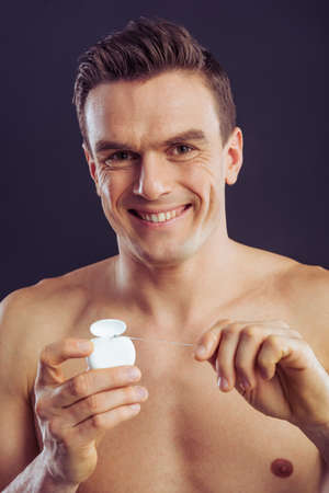 Portrait of handsome man using dental floss, looking at camera and smiling, on a dark background