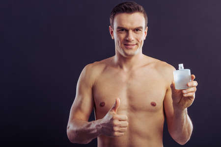 aftershave: Handsome man holding aftershave lotion, showing Ok sign and smiling, on a dark background