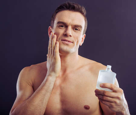 aftershave: Portrait of handsome man holding aftershave lotion and applying it, on a dark background