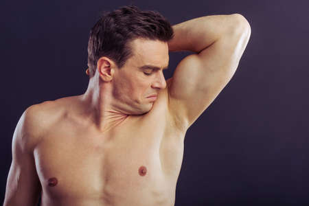 underarm: Portrait of handsome man smelling his underarm, on a dark background Stock Photo