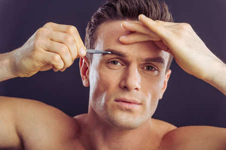 pluck: Portrait of handsome man plucking his eyebrows, on a dark background